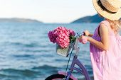 Little Lady With Bicycle And Pink Flowers On Sea Beach. Kid Girl In Straw Hat And Dress Is Riding On poster