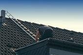 Roofer Works On An Unfinished Roof. Installs Roof Shingles poster