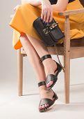 Girl With A Fashionable Handbag On The Chair. Girl In Sandals. Handbag In The Hands Of The Girl. Gir poster