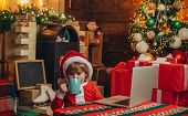 Boy Child With Laptop Near Christmas Tree. Buy Christmas Gifts Online. Christmas Shopping Concept. G poster
