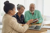 Side view of financial adviser discussing information with a African-American couple indoor. Authent poster
