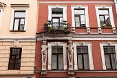 Beautiful Facade Of An Old Building With An Elegant Balcony With Flowers And Two Caryatids poster