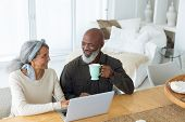 Front view of diverse senior couple using laptop on table while man holds a cup in beach house. Auth poster