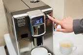The Girl Chooses The Mode Of Making Coffee On The Coffee Machine. Female Hand Presses The Button On  poster