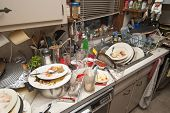 picture of sink  - Pile of dirty dishes in sink and counter top after a party - JPG