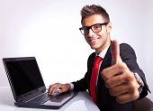 picture of gesture  - side view of a business man working on laptop and making the ok gesture - JPG
