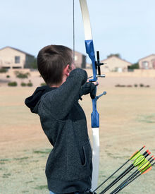 pic of fletching  - Young boy archer drawing back a bow and arrow - JPG