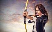 image of pulling  - beautiful career woman pulls arrow with a bow - JPG
