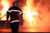 stock photo of firemen  - Fireman fighting a raging fire with huge flames of burning car - JPG