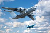 stock photo of awacs  - Two planes fly in formation against the picturesque sky. A-50 (base IL-76) and Su-27 (Flanker).
