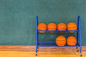 stock photo of basketball  - Basketballs are resting in a blue metal storage rack along a blue green wall and on a wooden gym floor - JPG