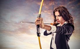foto of bow arrow  - beautiful career woman pulls arrow with a bow - JPG