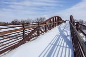 foot and bike trail bridge in winter scenery - South Platte River at Fort Lupton, Colorado