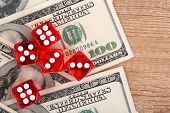 Red dices and dollars on wooden background