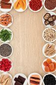 Healthy superfood abstract border over oak wood background