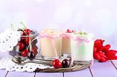 Delicious yogurt with fruits tastes in glasses and fresh fruits on napkin, on color wooden table, on