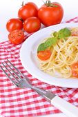 Delicious spaghetti with tomatoes on plate on table close-up
