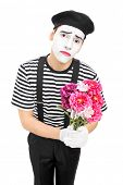Sad mime artist holding a bouquet of flowers isolated on white background