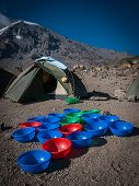 pic of kilimanjaro  - Washing bowls for trekkers at Karanga campsite on Kilimanjaro Machame route with glaciers of southern icefields on the rim of Kilimanjaro in background - JPG