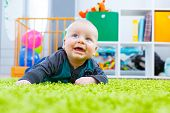 Infant crawling on the green carpet in the child room