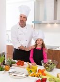 Chef master and junior pupil kid girl at cooking school with food on countertop