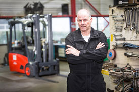 stock photo of forklift  - middle aged mechanic standing in a forklift garage in his uniform with a forklift and his repair tools in the background - JPG