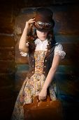 image of outfits  - Portrait of a young woman wearing a steampunk outfit and holding a portfolio bag - JPG