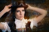 image of lolita  - Portrait of a young woman wearing a steampunk outfit with top hat and aviator glasses - JPG