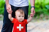 picture of flag confederate  - Toddler in Switzerland Flag shirt walking supported by his father - JPG
