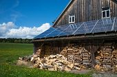 pic of roof-light  - solar power panels on barn roof with stacked fire wood in front - JPG