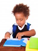 stock photo of first class  - Portrait of sweet little black boy reading books isolated on white background - JPG