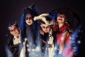 stock photo of witchcraft  - Cheerful children in halloween costumes posing over dark background - JPG