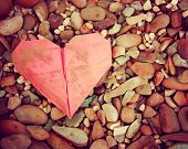 stock photo of discard  -  a discarded paper heart on a rock background toned with a retro vintage instagram filter effect  - JPG