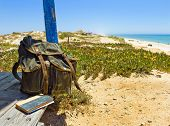 picture of beach hut  - Backpack and book on the porch of a wooden hut next to the shore of a European beach. Backpacking traveller taking a break in a tour through Algarve Portugal. (Tavira beach in Tavira island)
