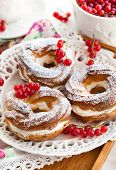 stock photo of cream puff  - Cream puff rings (choux pastry) decorated with fresh red currant