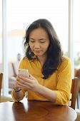 foto of handphone  - Young Attractive Woman Texting Her Handphone At Cafe