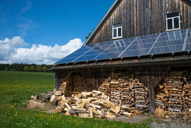 picture of barn house  - solar power panels on barn roof with stacked fire wood in front - JPG