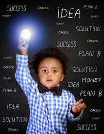 image of schoolboys  - Portrait of little African genius boy with lightbulb in the hand on blackboard background - JPG