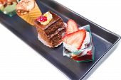foto of fancy cake  - top of view of delicious strawberry cake near chocolate and coffee cakes on black dish - JPG