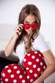 stock photo of flirty  - Portrait of a Flirty Woman In Heart Shaped Glasses - JPG