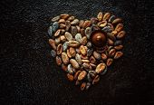 stock photo of cocoa beans  - Cocoa beans in the shape of hearts on a dark background - JPG