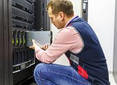 stock photo of chassis  - young man IT engineer repair server in the data center