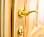 foto of door-handle  - Golden door handle and lock on the new wooden door in the joiner