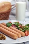 picture of wieners  - Wiener sausage with ketchup, mustard and salad.