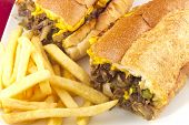 pic of cheesesteak  - A messy Philly Cheesesteak with onions peppers and mushrooms fries on the side