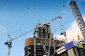 foto of highrises  - Highrise Construction Site with Many Lifting Cranes - JPG