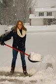 stock photo of snow shovel  - A young woman happy to be shoveling snow in a blizzard - JPG