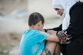 picture of arabic woman  - Arabic Muslim Middle Eastern poor woman with her son on dirty ground - JPG