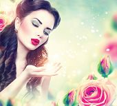 picture of blowing  - Retro woman portrait in beauty pink roses garden - JPG