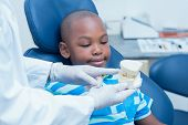 stock photo of prosthesis  - Cropped dentist showing young boy prosthesis teeth in the dentists chair - JPG